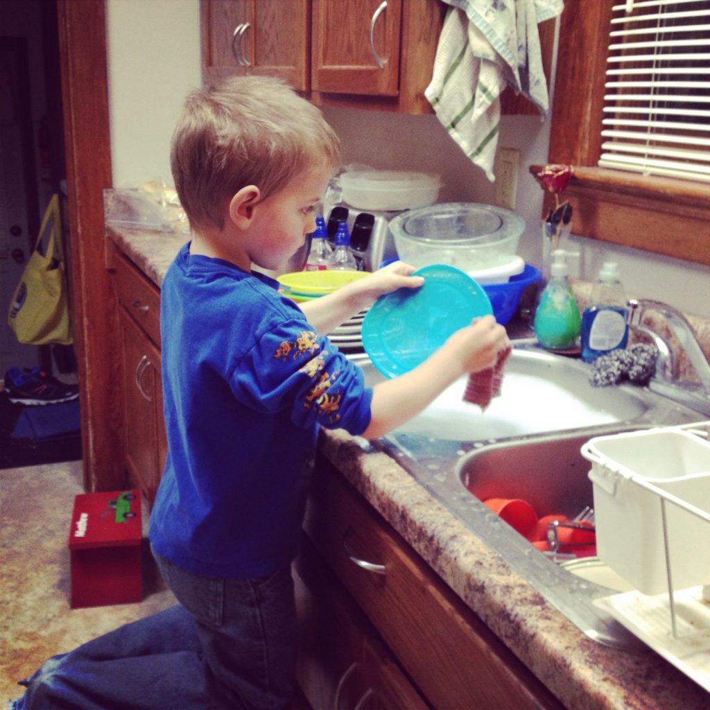 A young boy washing a plate at a sink full of soapy water.