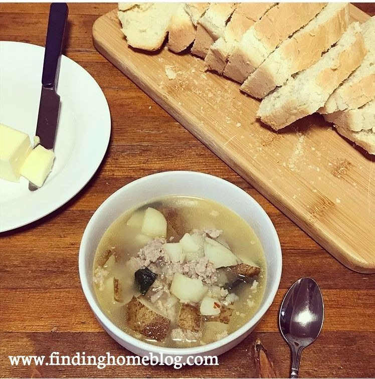 A bowl of soup with sausage, potatoes, and spinach in the foreground, with a spoon next to it. Sliced bread on a cutting board, and a plate with butter and a knife in the background.