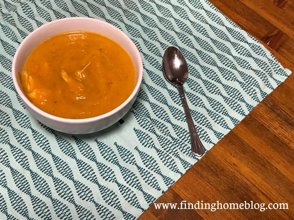 A bowl of vibrant orange soup on a blue patterned cloth with a spoon next to it