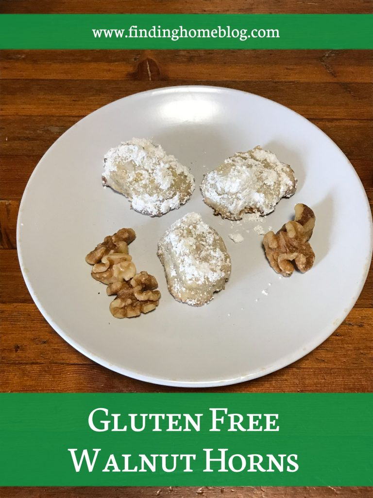 Three cookies, coated with powdered sugar, on a plate, along with some walnuts