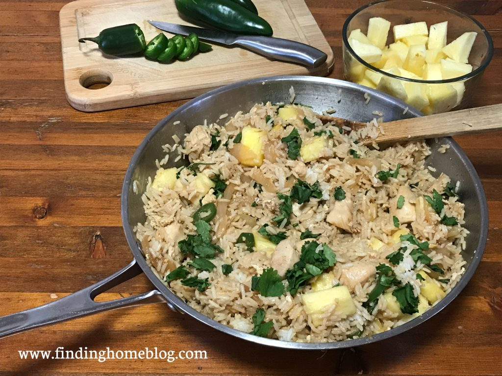 In the foreground, a large skillet with fried rice, jalapeños, and pineapple in it, and a wooden spoon. In the background, a cutting board with a knife and sliced jalapeños, and a glass dish holding chopped pineapple.