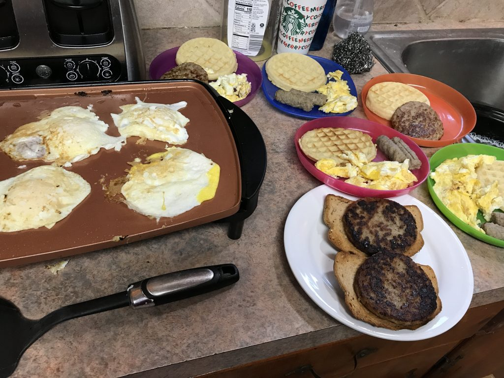 Several plates of breakfast foods: sausage, eggs, waffles, and toast, next to a griddle with more eggs cooking.