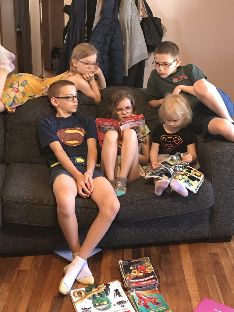 Five kids reading books together on a couch.