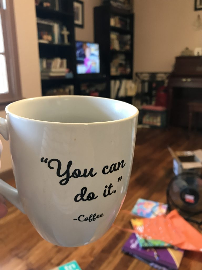 """A close up of a coffee mug that says """"You can do it. - Coffee"""", with the television on in the background, playing The Magic School Bus."""