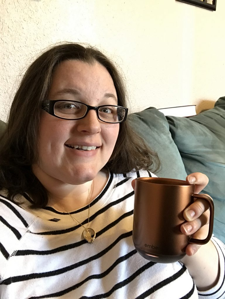 A woman smiling and holding an Ember coffee mug.