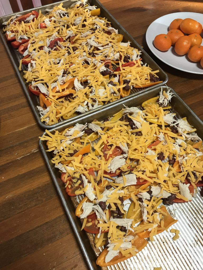 Two sheet pans of nacho toppings on halved mini peppers, before being baked.