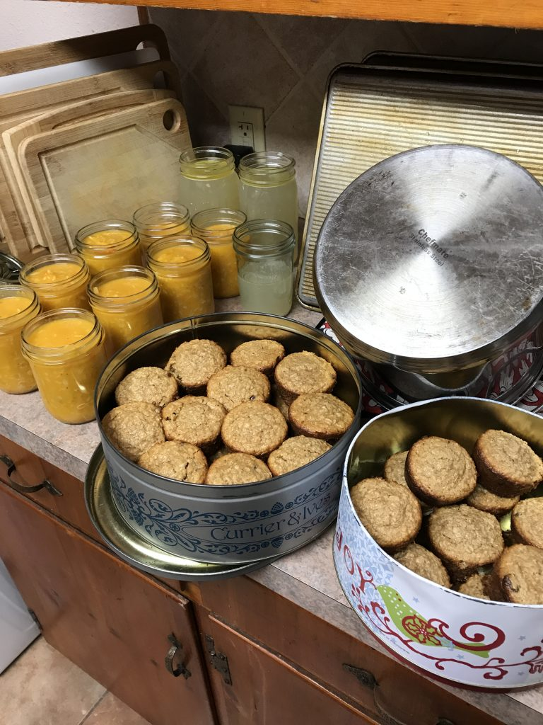 Glass jars full of a butternut soup and broth, two containers of muffins. Some clean dishes in the background.