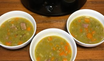 "A crockpot full of split pea soup, with three bowls dished out in front of it. A banner reads ""Crockpot Ham and Split Pea Soup"""