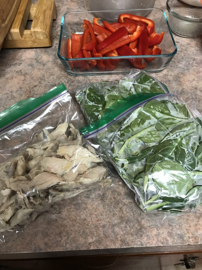 Chopped cooked chicken in a ziploc bag, 2 bags of chopped spinach nearby. A container of sliced red peppers in the background.