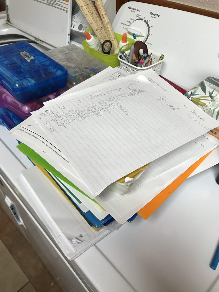 Stack of papers and school books on a dryer.