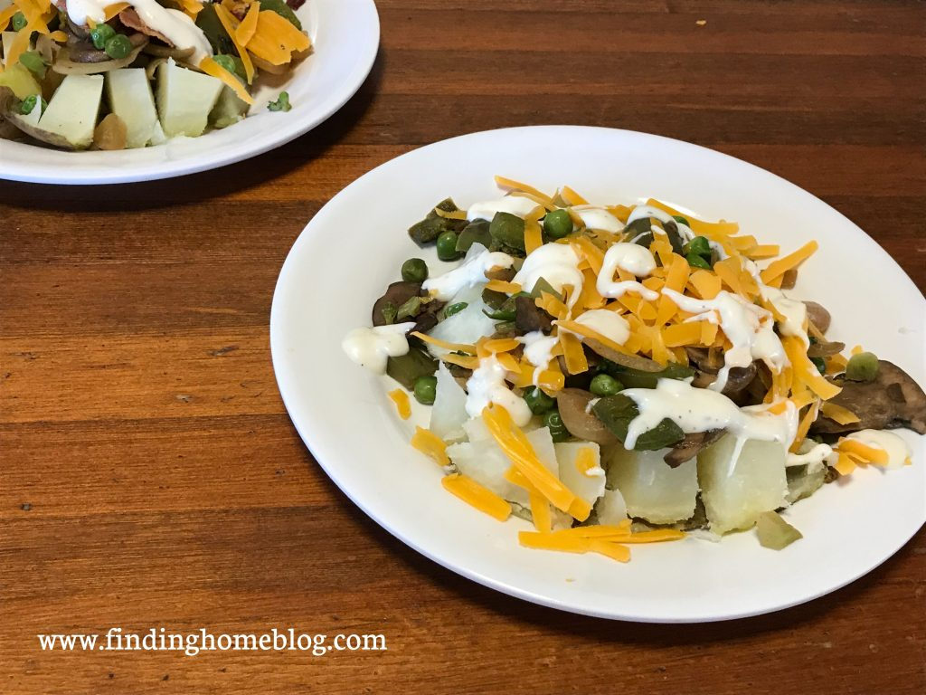 A plate with a baked potato loaded with toppings, including bell peppers, peas, broccoli, and mushrooms, as well as cheese and ranch dressing.