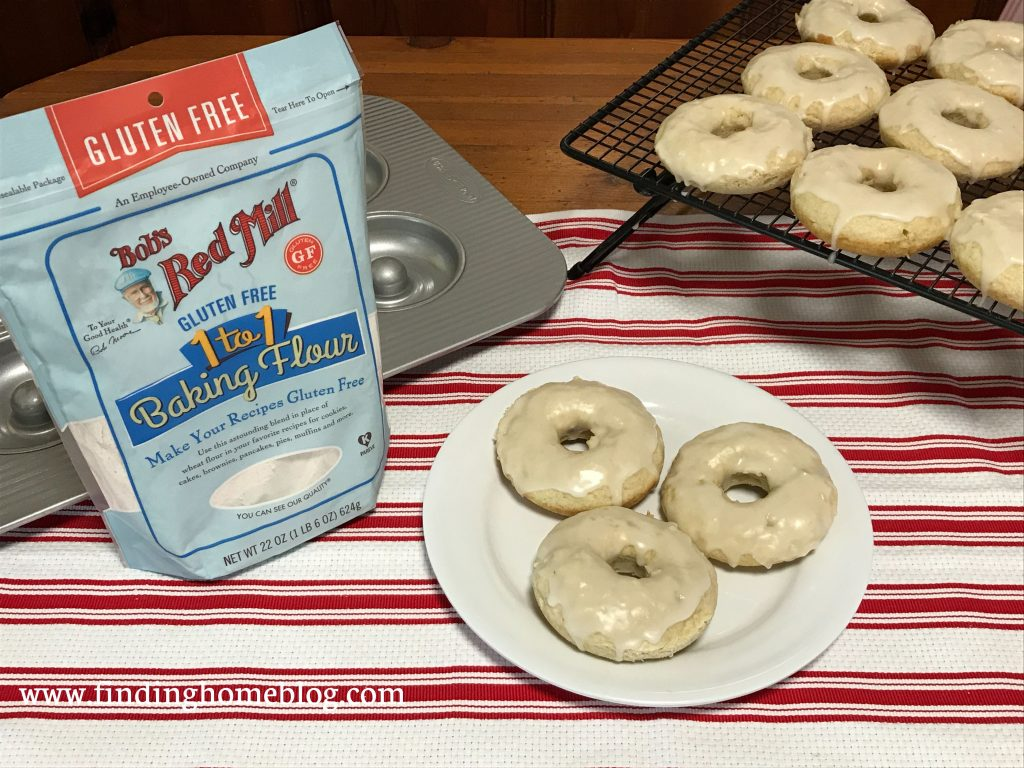 A plate with three glazed cake donuts on it in the center, with a cooling rack holding more donuts off to the right. A package of Bob's Red Mill gluten free 1-to-1 baking flour and a donut pan off to the left.