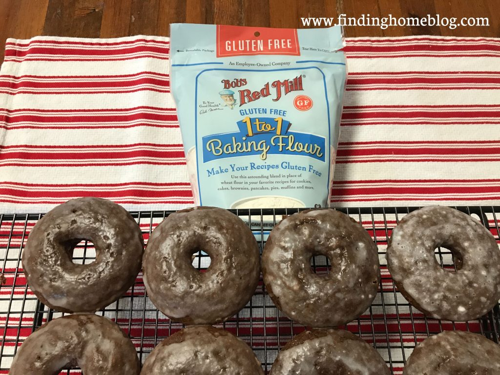 An overhead shot of four chocolate glazed donuts on a cooling rack, with a package of Bob's Red Mill 1-to-1 Gluten Free Baking Flour in the background.