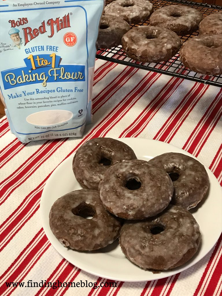 A plate of several glazed chocolate donuts in the foreground, with more on a cooling rack in the background, along with a package of Bob's Red Mill Gluten Free 1-to-1 Baking Flour.