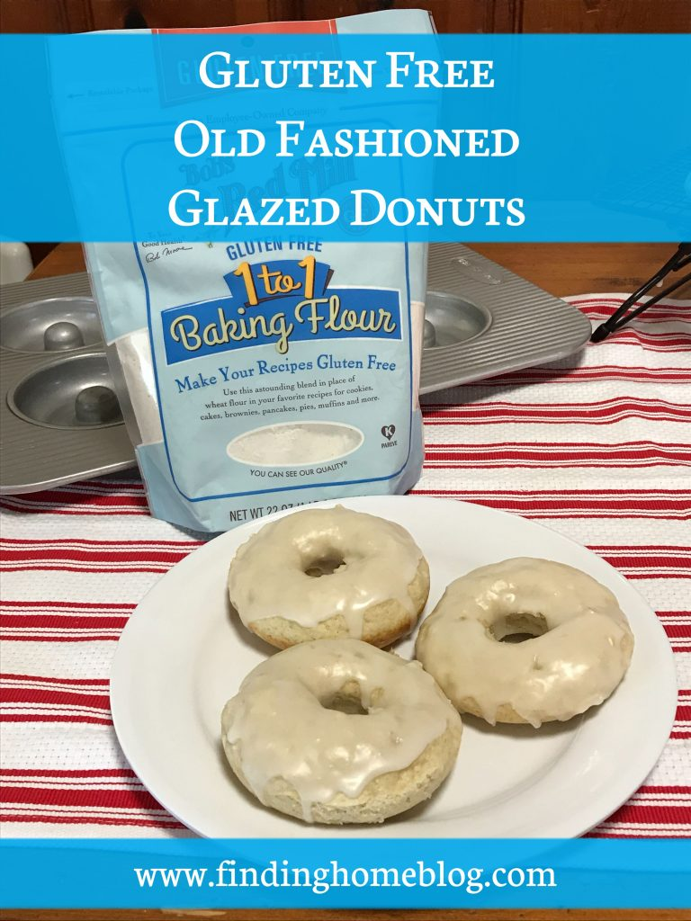 """Close up on a plate of three glazed cake donuts. Behind is a package of Bob's Red Mill gluten free 1-to-1 baking flour and a donut pan. A banner across the top reads """"Gluten Free Old Fashioned Glazed Donuts"""""""