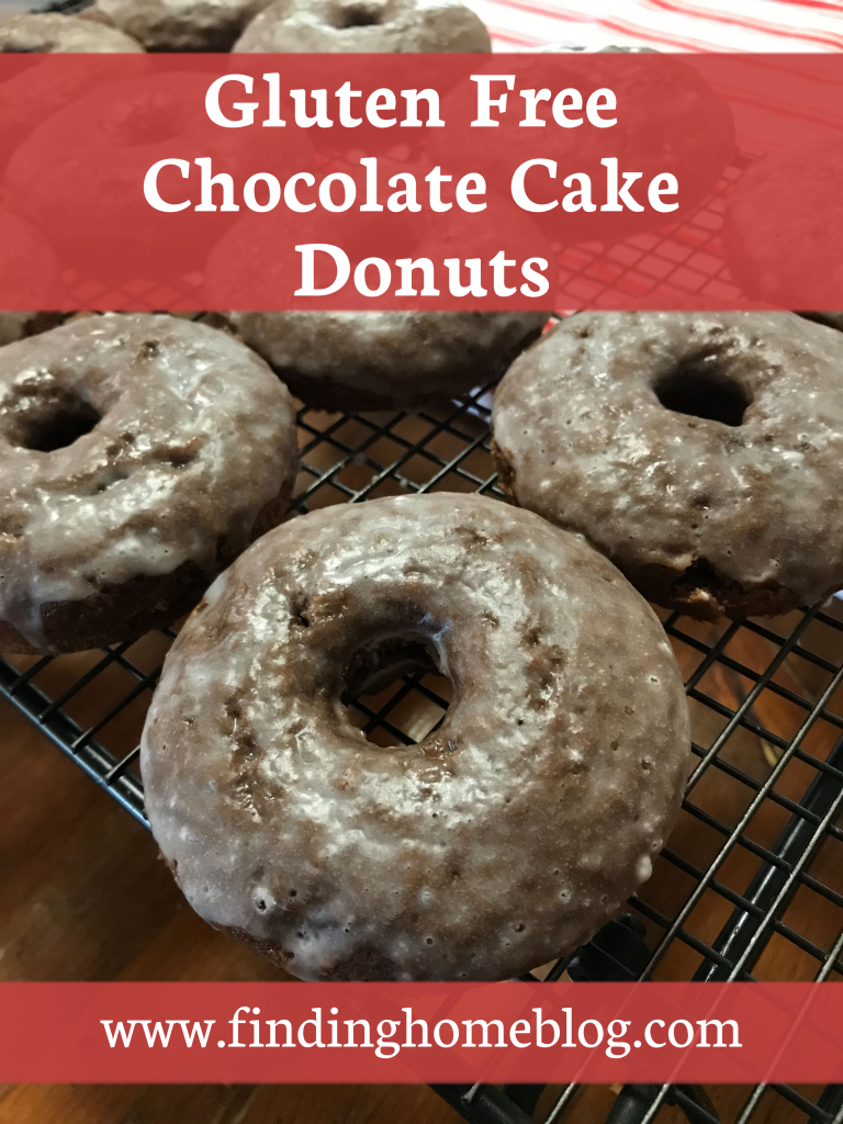 """A close up of glazed chocolate cake donuts on a cooling rack. A banner reads """"Gluten Free Chocolate Cake Donuts""""."""