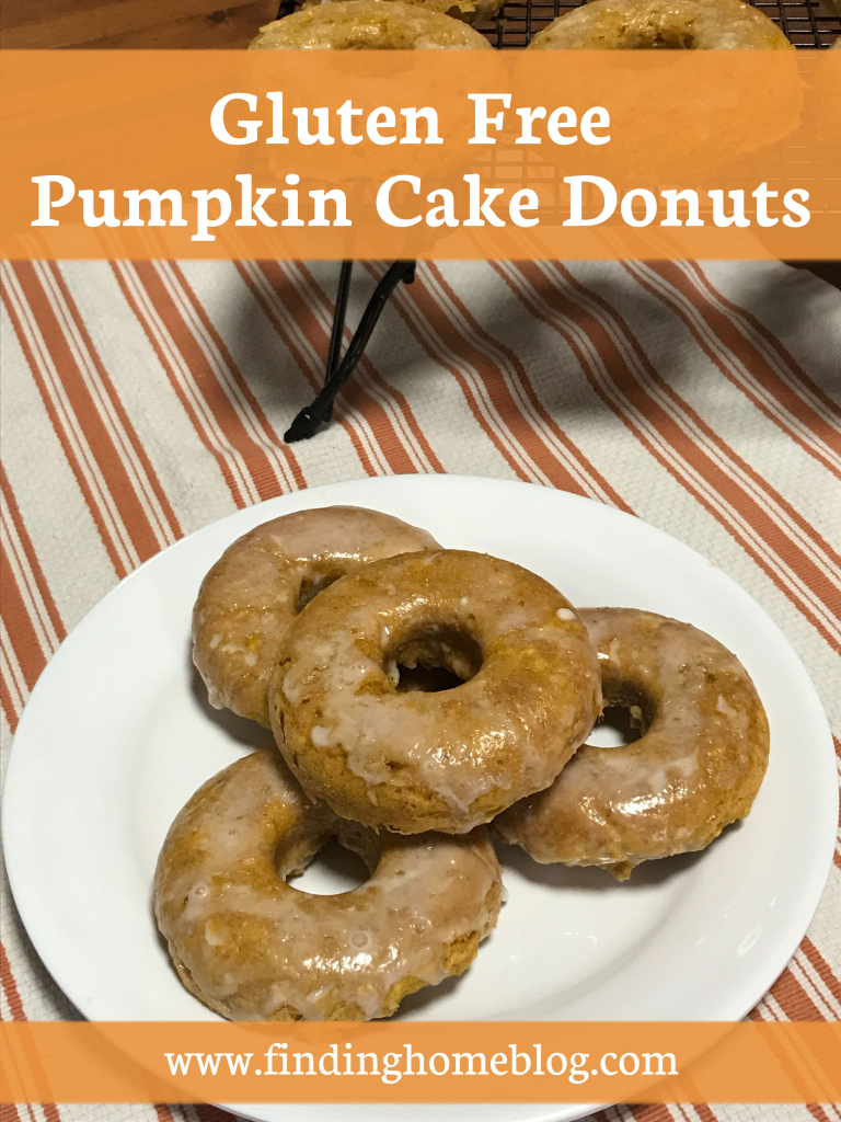 """A plate of pumpkin glazed donuts sitting on a cloth, with more donuts on a rack in the background. A banner reads """"Gluten Free Pumpkin Cake Donuts"""""""