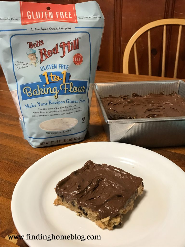 In the foreground, a peanut butter chocolate chip bar with chocolate frosting on a plate. The pan of bars is in the background. Off to the left is a package of Bob's Red Mill 1-to-1 gluten free flour.