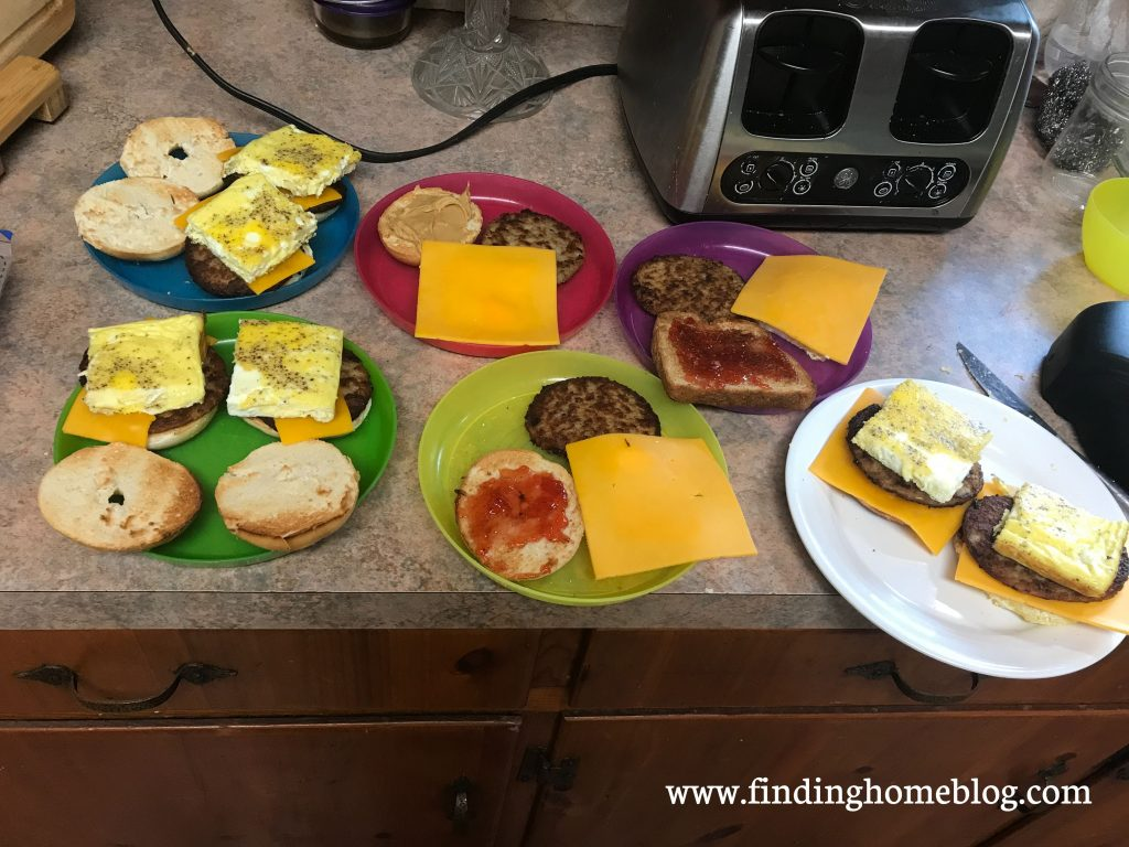 Several plates with breakfast sandwiches in various states of assembly (eggs, cheese, sausage patties, on bagels). A toaster is nearby.