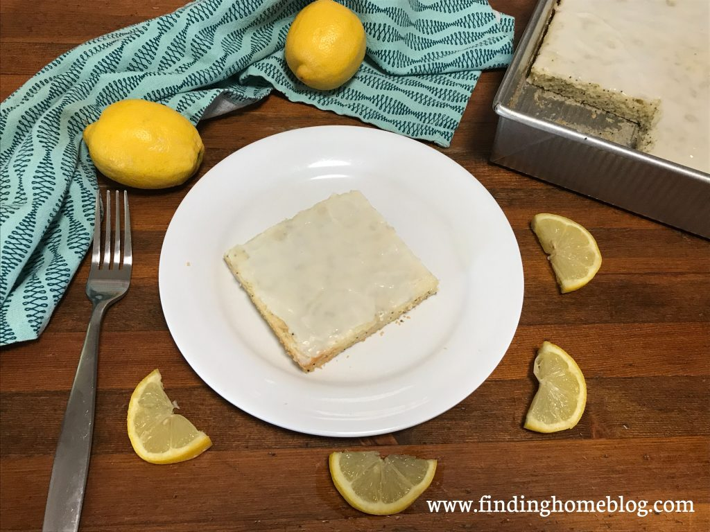 A piece of lemon cake on a plate, surrounded by lemon slices, whole lemons, a cloth napkin, and the pan of cake.