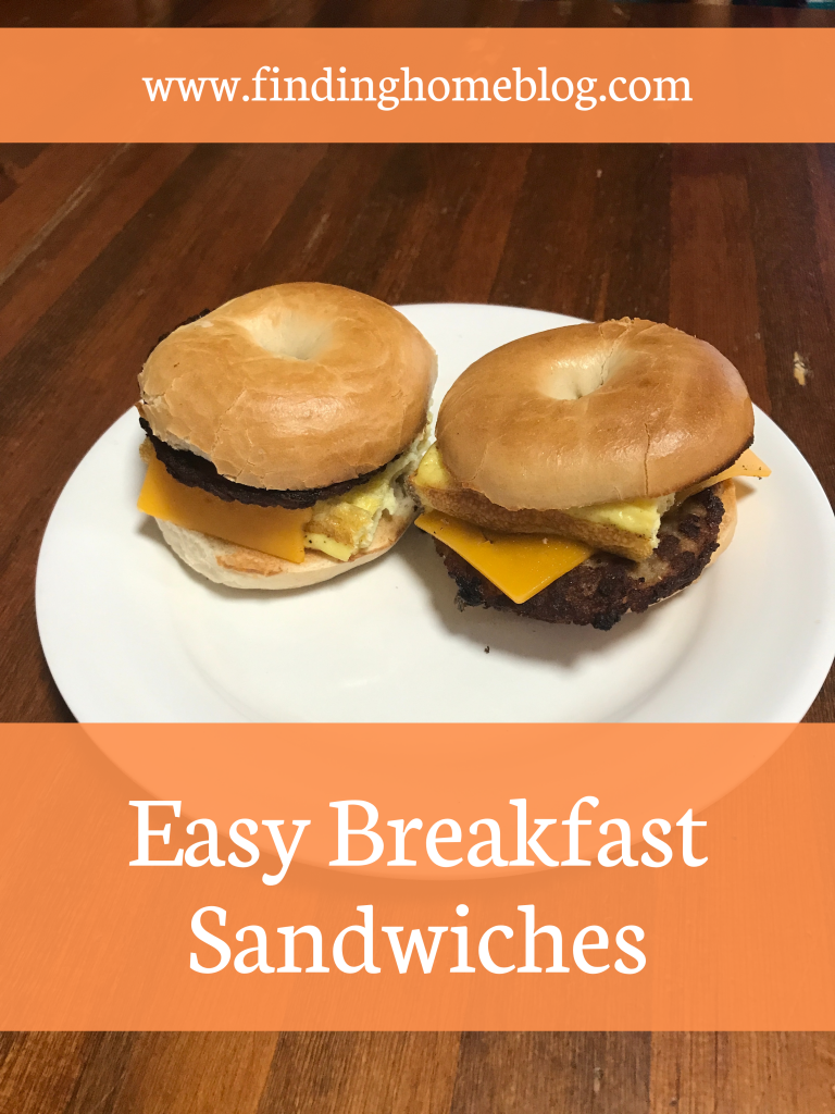 """A plate with two breakfast sandwiches (bagel, egg, sausage patty, and cheese). A banner below reads """"Easy Breakfast Sandwiches""""."""