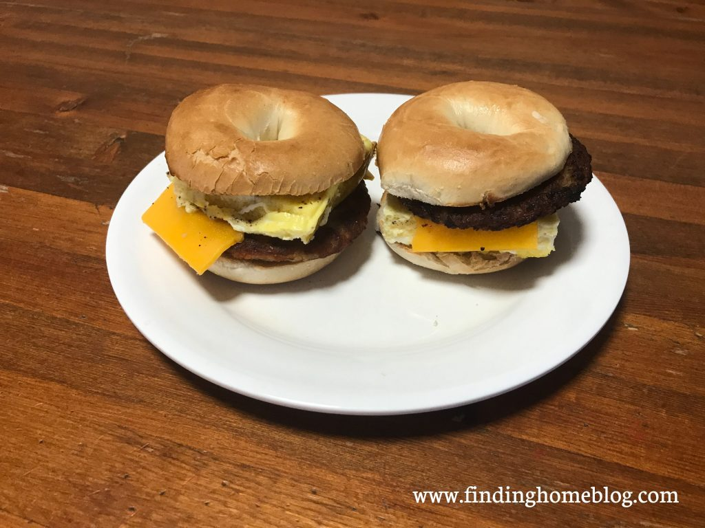 Two breakfast sandwiches on a plate, made up of bagels, sausage patties, cheese slices, and scrambled eggs.